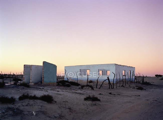 Vista exterior del edificio abandonado en el desierto al atardecer - foto de stock