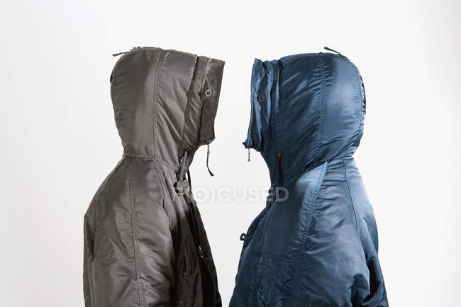 Two men wearing hooded parkas standing face to face on white background — Stock Photo
