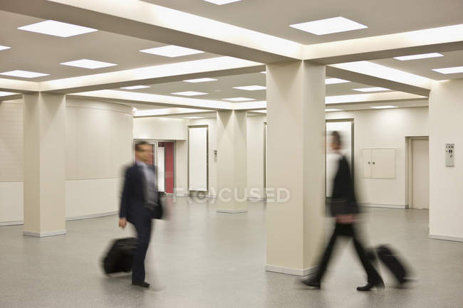 Businessmen pulling suitcases walking in different directions — Stock Photo