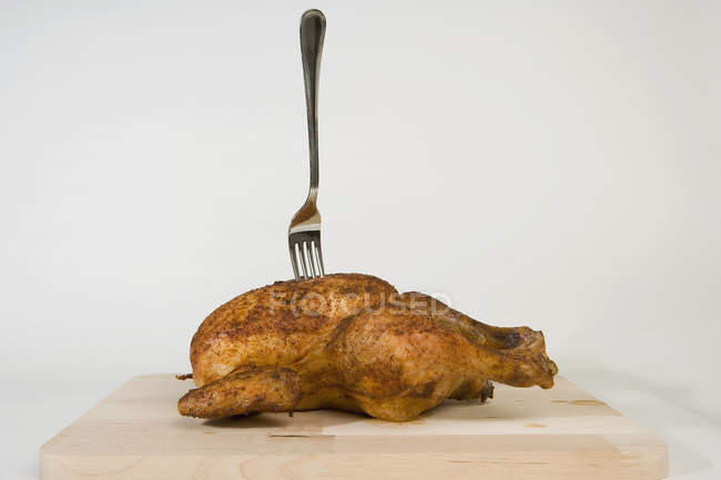 Fork stuck in roast chicken on wooden board over white — Stock Photo