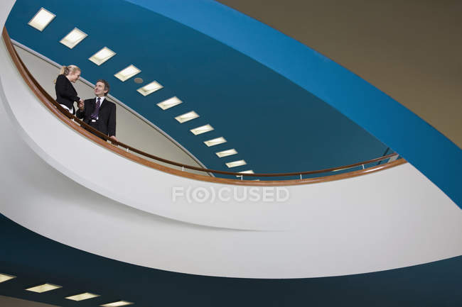 Two business people standing on a balcony and shaking hands — Stock Photo