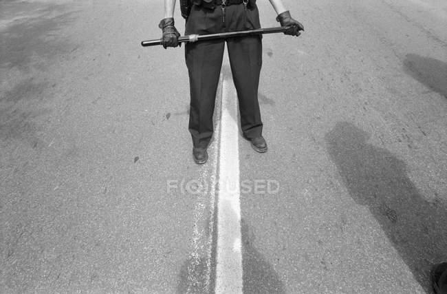 Baixa seção de policial de pé na estrada e segurando bastão — Fotografia de Stock