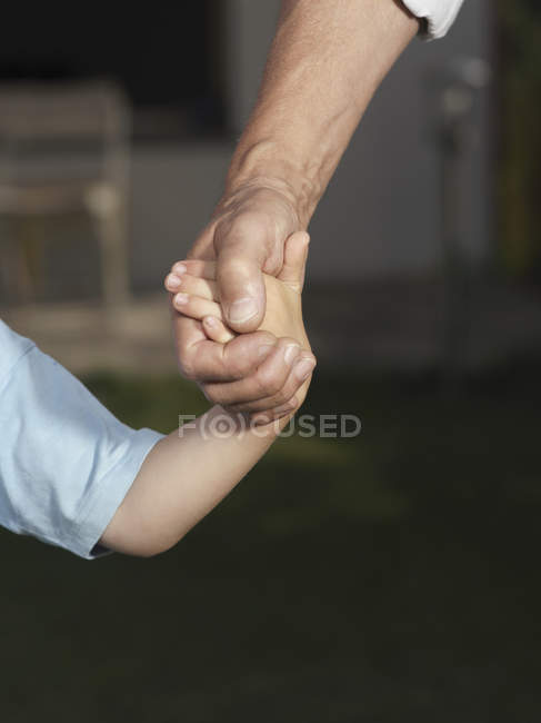 Cropped image of child and man holding hands — Stock Photo