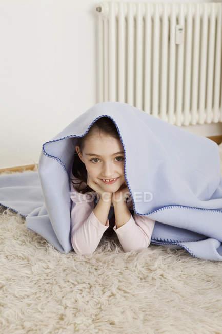 Menina sorridente escondido debaixo do cobertor e olhando para a câmera — Fotografia de Stock