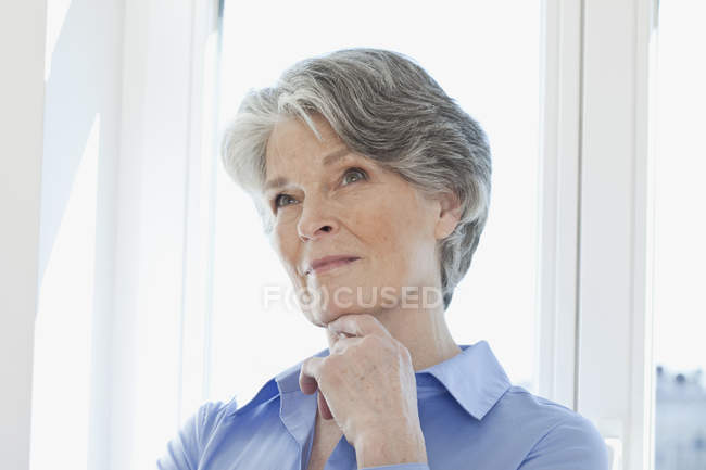 Portrait of thoughtful senior woman in front of window — Stock Photo