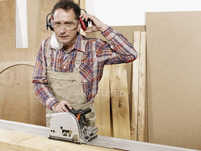 Portrait of man using circular saw in workshop — Stock Photo