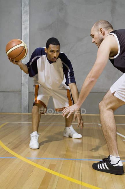 Un giocatore di basket dribbling la palla e un altro giocatore lo custodisce — Foto stock