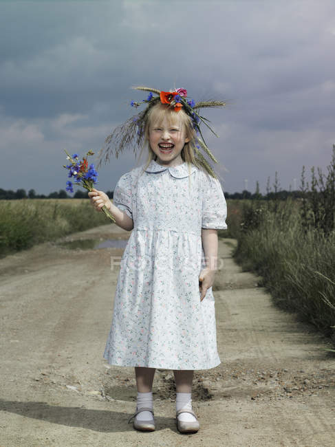 A girl standing on a country road and holding wildflowers — Stock Photo