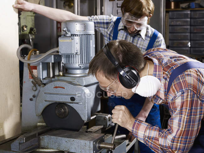 Man using electric saw in workshop while young man watching — Stock Photo