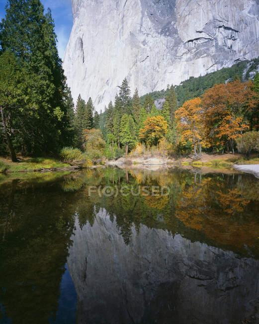 Montaña reflejada en el lago tranquilo con árboles coloridos en la costa - foto de stock