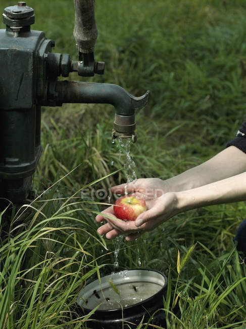 Crop hands washing apple underneath outdoor tap — Stock Photo