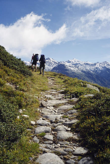 Rear view of two people hiking up mountain path — Stock Photo