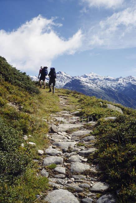 Vista posterior de dos personas, ir de excursión por camino de montaña - foto de stock