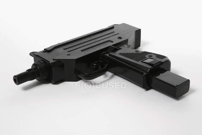 Schwarze Kunststoff-Spielzeugpistole auf weißem Hintergrund — Stockfoto
