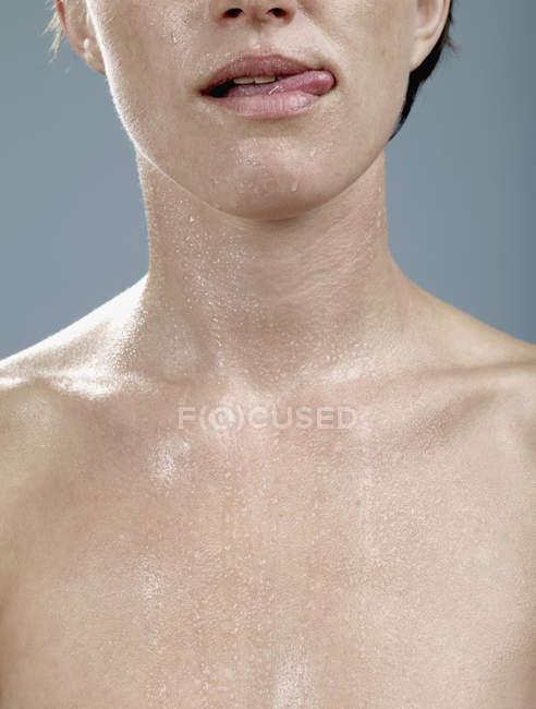 Una mujer con la piel mojada lamiendo sus labios - foto de stock
