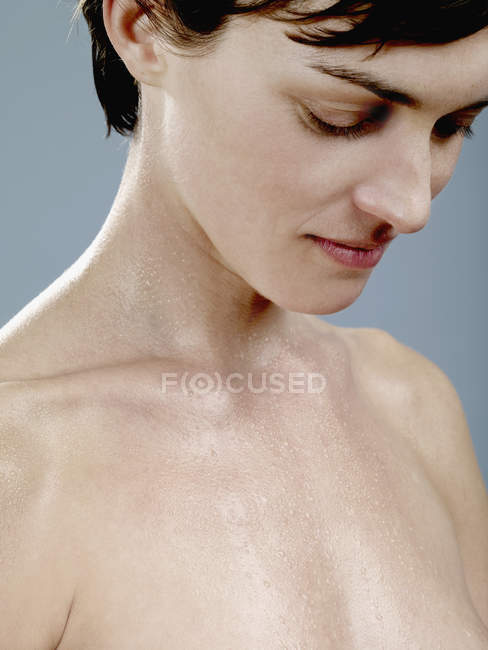A woman with wet skin looking down — Stock Photo