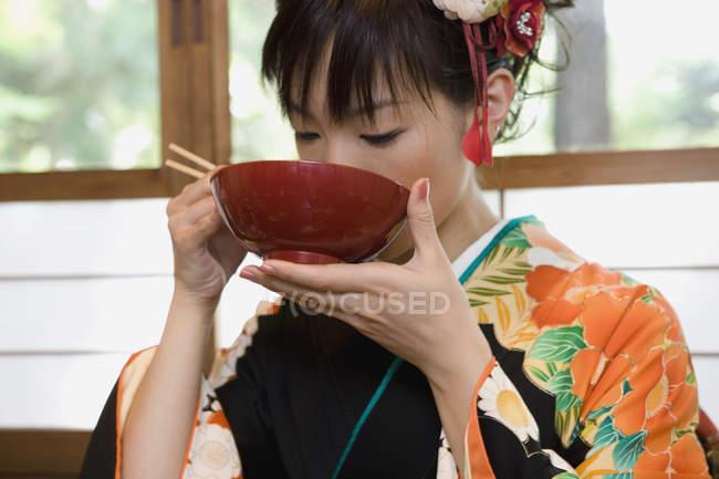 Eine Frau trägt einen Kimono und isst Suppe — Stockfoto