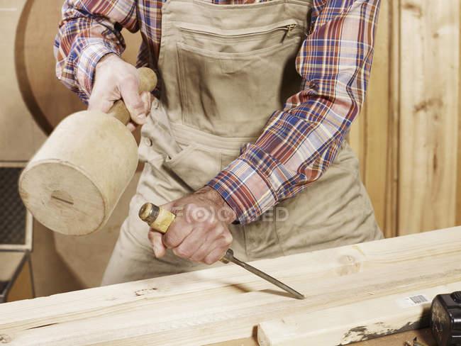 Mann meißelt Holz auf Werkbank — Stockfoto