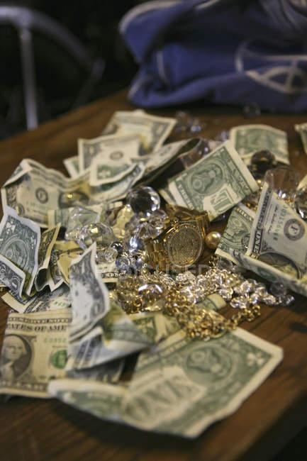 Zerknüllte Banknoten und Schmuck auf dem Tisch — Stockfoto