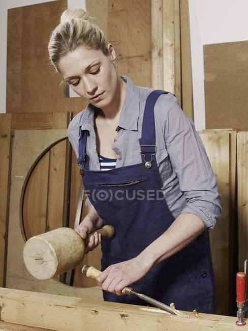 Jeune femme ciselant du bois en atelier — Photo de stock