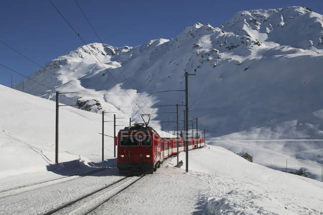 Train traveling through mountain pass in winter — Stock Photo