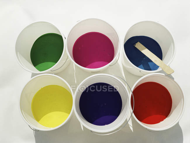 High angle view of buckets with various colors of paint — Stock Photo