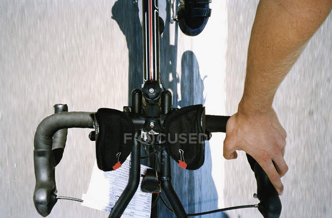 Looking down view of cyclist's hand on bike handlebar — Stock Photo