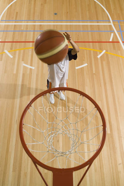 Basketball in mid-air by indoor basketball hoop — Stock Photo