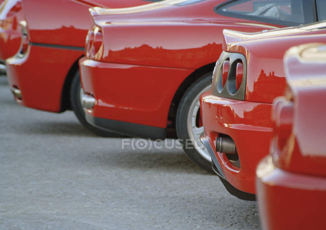 Cropped image de voitures neuves rouges garée en ligne — Photo de stock