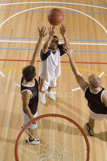 Ein Basketballspieler schießt den Basketball, während zwei weitere Spieler versuchen, seinen Schuss zu blocken — Stockfoto