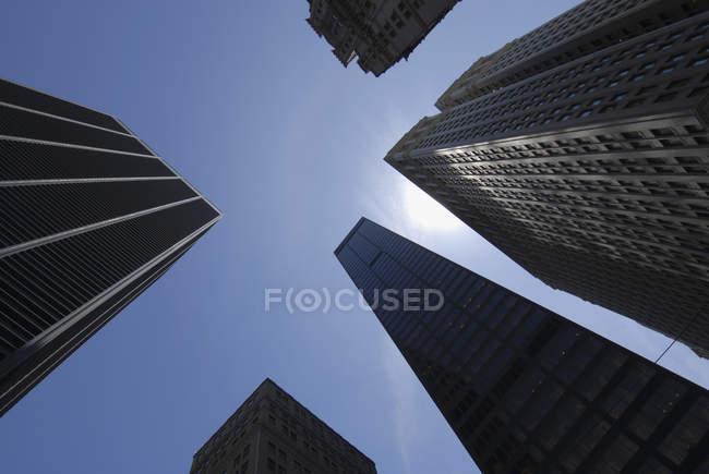 Vista inferior de arranha-céus sobre céu ensolarado e claro — Fotografia de Stock