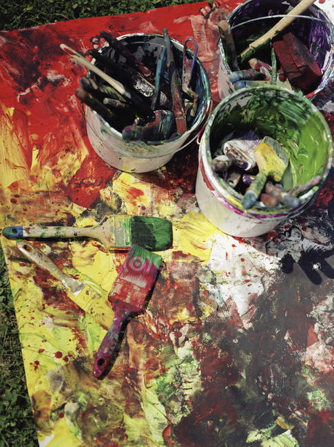 Close up view of messy buckets of paint and paintbrushes — Stock Photo