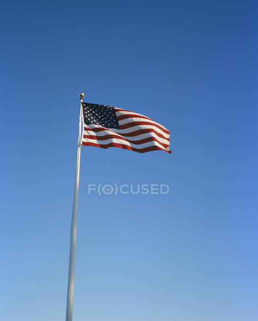 Sunlit American flag flapping in sky — Stock Photo
