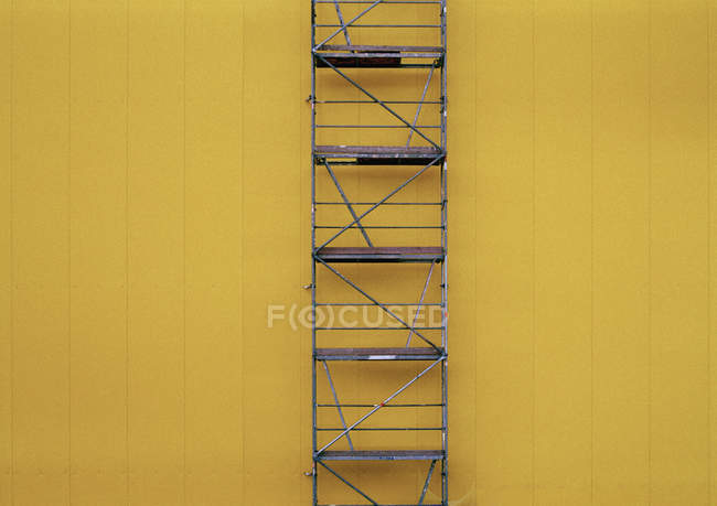 Full frame shot of scaffolding against yellow wall — Stock Photo