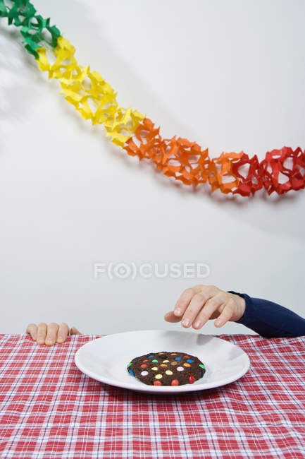 Male hand from bellow table reaching for cookie on plate — Stock Photo