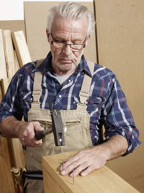 Senior man hammering nails into wood in workshop — Stock Photo
