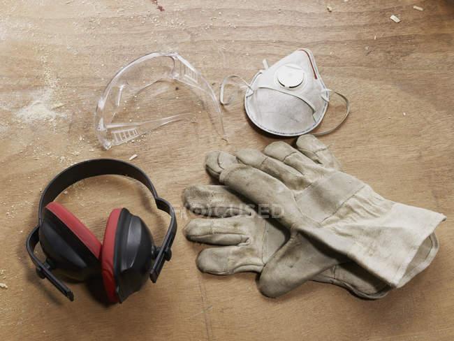 Vêtements de travail protecteurs sur table en bois — Photo de stock
