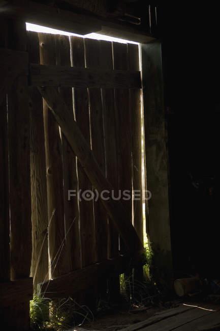 Luce che splende attraverso la porta di buio capannone — Foto stock