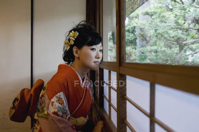 A woman wearing a kimono and looking out of a window — Stock Photo