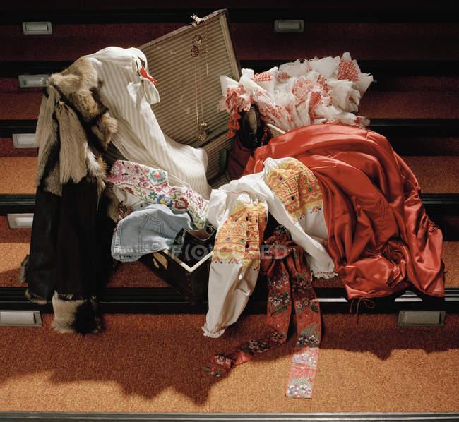 Костюмы, вываливающиеся из открытого чемодана на ступеньках — стоковое фото