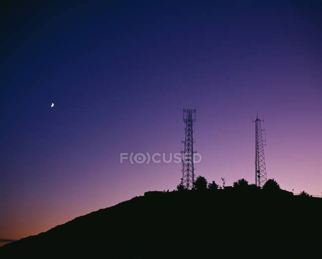 Silhouettes of transmission towers on hill at dusk — Stock Photo