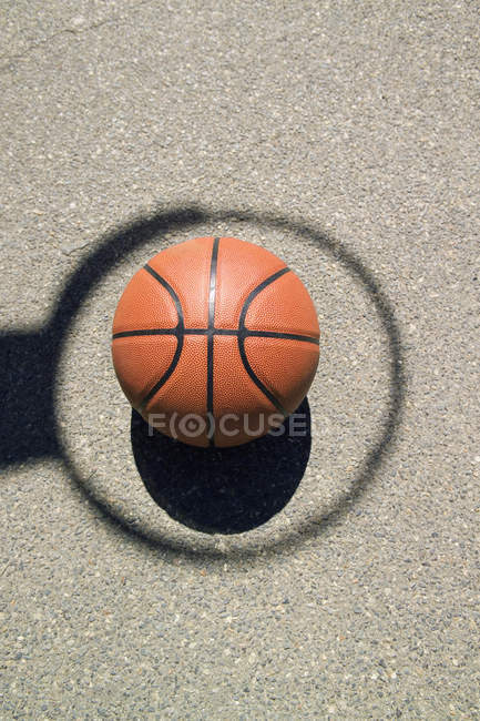 Basketball on asphalt in middle of shadow hoop — Stock Photo