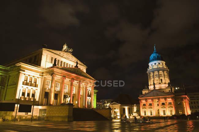 Blick zum Gendarmenmarkt mit beleuchteten Fassaden des ehemaligen Schauspielhaus und der französischen Kirche in Berlin, Deutschland — Stockfoto
