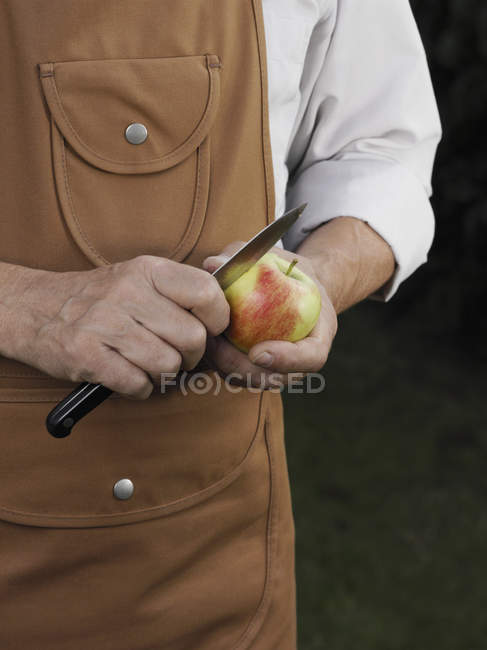 Mid section of man in apron cutting apple — Stock Photo