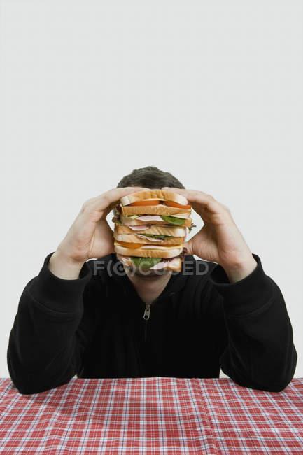 Retrato do homem sentado à mesa e escondendo o rosto por trás da grande sanduíche — Fotografia de Stock