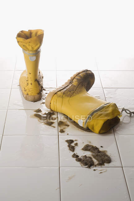 Pair of muddy rubber boots on tiled floor — Stock Photo
