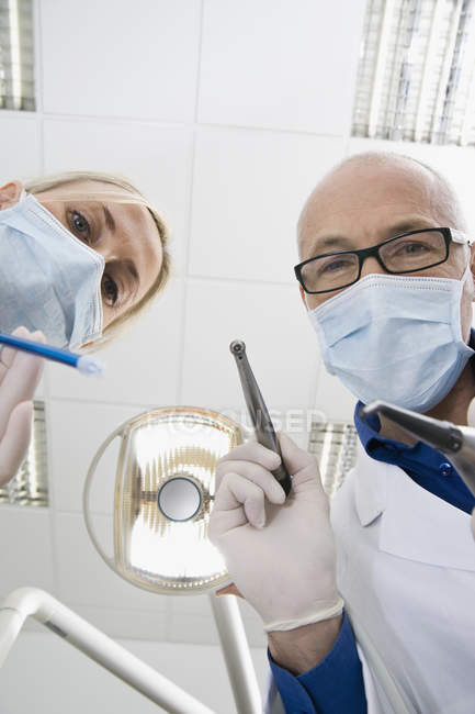 Dentist and assistant holding working tools and looking at camera — Stock Photo