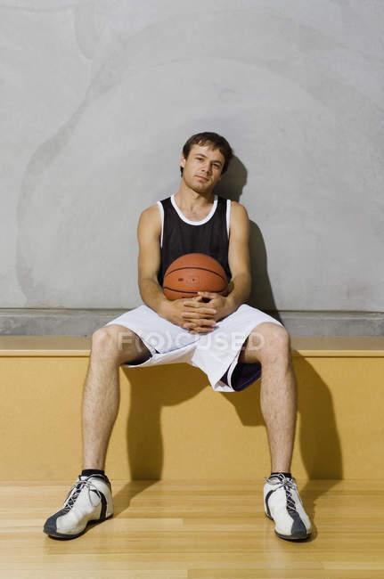 Um jovem sentado em um banco em um campo de basquete — Fotografia de Stock