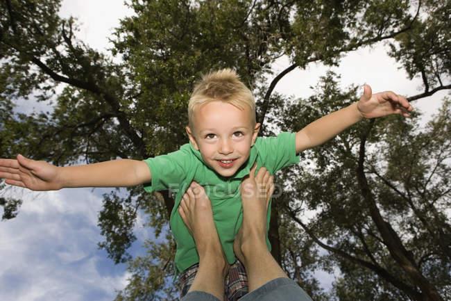 Jeune garçon équilibré sur les pieds avec les bras dehors — Photo de stock