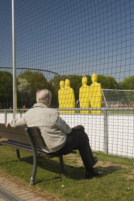 Vista trasera del hombre sentado en el banco y viendo la práctica del fútbol - foto de stock